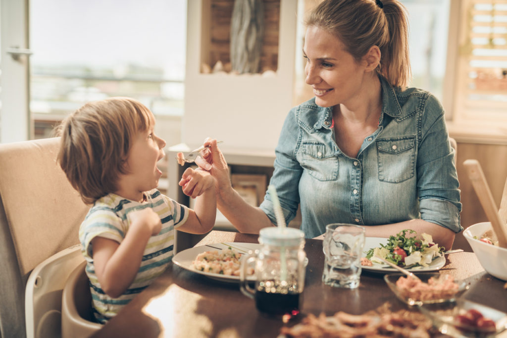 mother feeding foster child at table with food from support group